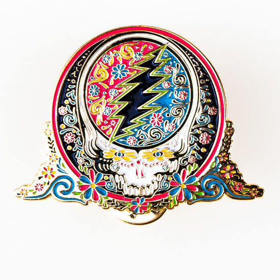 Enamel pin of a Grateful Dead Steal Your Face skull with a colorful Day of the Dead inspired calaveras design, with a pink and blue background inside the skull, a white skull, and a black background outside the skull