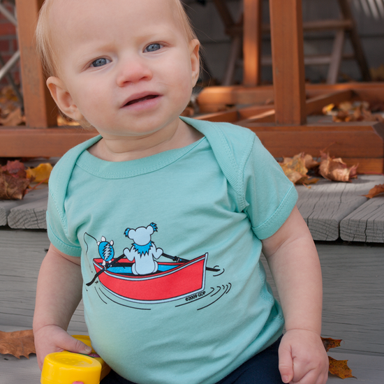 A baby boy sitting on wooden deck steps, wearing a blue Terrapin and Bear Dinghy infant one piece.