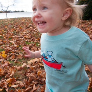 Young toddler running in fall leaves, wearing a light blue Terrapin and Bear Dinghy toddler tee.
