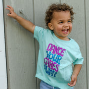 "Little boy standing in front of a grey wall, wearing a light blue toddler tee that says, ""Dance your cares away"" in purple and blue"