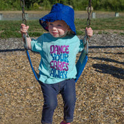 "Little girl on a playground swing, wearing a blue sun hat and a light blue toddler tee that says, ""Dance your cares away"" in purple and blue"