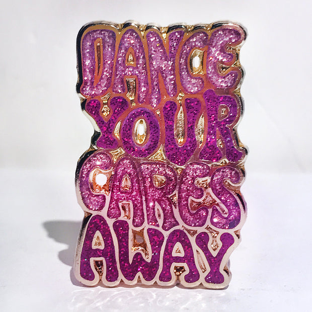 "Enamel pin that says, ""Dance your cares away"" in magenta and pink"