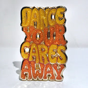 "Enamel pin that says, ""Dance your cares away"" in yellow and orange"