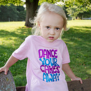 "Blonde girl leaning against a railing in front of grass and a tree, wearing a pink toddler tee that says, ""Dance your cares away"" in purple and blue"