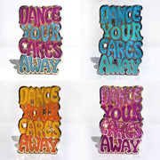 "Four enamel pins that say ""Dance your cares away."" One in magenta and teal, one in blue and green, one in yellow and orange, and one in magenta and pink."