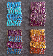 "Four enamel pins, laying on granite, that say ""Dance your cares away."" One in magenta and teal, one in blue and green, one in yellow and orange, and one in magenta and pink."