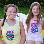 "Two girls sharing an Adirondack chair in the grass, wearing yellow and pink racer back tanks that say ""Dance your cares away"" in purple and blue"