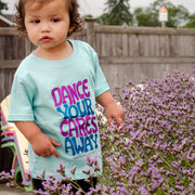 "Little girl standing among purple flowers in front of a wooden fence, wearing a light blue toddler tee that says, ""Dance your cares away"" in purple and blue"