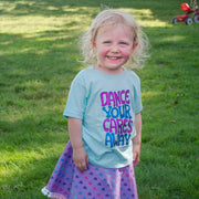 "Smiling little girl standing in the grass, wearing a Light blue toddler tee that says, ""Dance your cares away"" in purple and blue, and a purple Little Hippie toddler skirt with hearts"