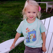 Blonde girl sitting on an Adirondack chair in grass, wearing a mint-colored Jim Henson's Fraggle Rock Music Note tshirt.