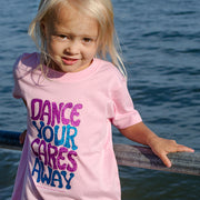 "Blonde girl leaning back on a railing in front of water, wearing a pink toddler tee that says, ""Dance your cares away"" in purple and blue"