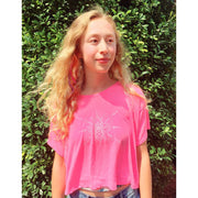 Blonde youth standing in front of foliage, wearing a pink women's boxy crop-style tshirt with mandala inspired infinity design