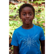Young boy standing in nature, wearing a neon blue youth tshirt with mandala inspired infinity design