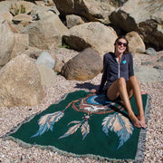 Smiling girl in sunglasses on a rocky beach, relaxing on a woven cotton blanket with a Grateful Dead Steal Your Face skull in a dream catcher with white and blue feathers hanging from it