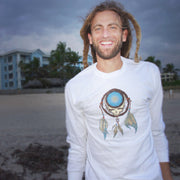 Bearded man in dreads, standing on the beach with houses in the background, wearing a Grateful Dead Steal Your Face skull in a dream catcher with white and blue feathers hanging from it, on a black unisex adult long sleeve tshirt