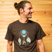 Man standing in front of a wooden wall, looking to his left and wearing a brown adult unisex tshirt with a Grateful Dead Steal Your Face skull in a dream catcher with white and blue feathers hanging from it