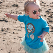 Toddler girl standing on a beach, wearing a turquoise Grateful Dead Steal Your Face Dreamcatcher toddler tshirt, a teal tutu, and baby aviators, pointing in the direction she wants to go
