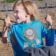 Little boy on a swing, looking off to the right, wearing a turquoise Grateful Dead Steal Your Face Dreamcatcher toddler tee.