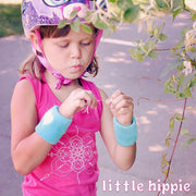 A young girl in a bicycle helmet on a sidewalk, wearing a pink girls tank with a mandala inspired infinity design