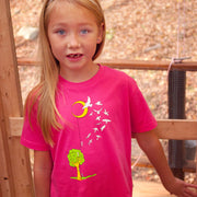 Blonde girl standing on a bridge, wearing our hot pink Flying People toddler tshirt