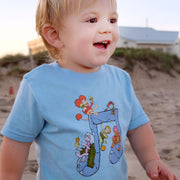 Toddler boy smiling on the beach, wearing a light blue Jim Henson's Fraggle Rock Music Note toddler tee.