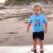 Little boy standing on the beach, looking like he was just startled by the ocean water over his feet, wearing a blue Jim Henson's Fraggle Rock Music Note toddler tee.