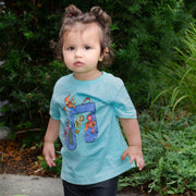Toddler standing in front of a large bush, wearing a mint colored Jim Henson's Fraggle Rock Music Note toddler tee.