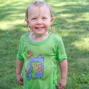 Grinning toddler standing in grass, soaking wet, wearing a green Jim Henson's Fraggle Rock Music note toddler tshirt.