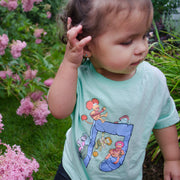 Toddler standing among pink flowers, wearing a mint colored Jim Henson's Fraggle Rock Music Note toddler tee.