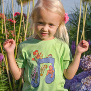 Blonde girl standing among tall flowers, wearing a green Jim Henson's Fraggle Rock Music Note toddler tee.