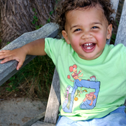 Grinning boy sitting on a weathered Adirondack chair, wearing a green Jim Henson's Fraggle Rock Music Note toddler tee.