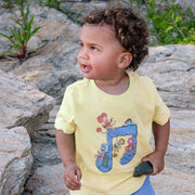 Little boy standing among large rocks, wearing a yellow Jim Henson's Fraggle Rock Music Note toddler tee.