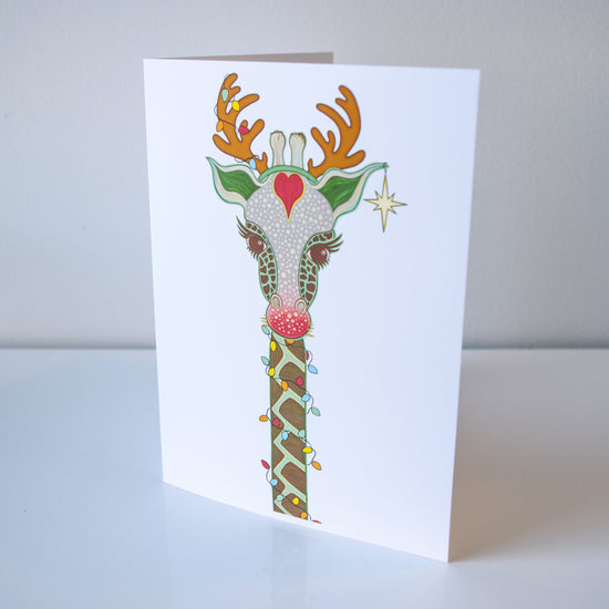 A white vertical greeting card with a giraffe in shades of brown and green, with a red nose, a red heart on it's forehead, Christmas lights spiraling up it's neck to it's horn, and a star hanging from it's ear