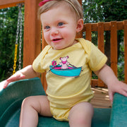 A baby girl sitting at the top of a slide, wearing a yellow Terrapin and Bear Dinghy one piece.