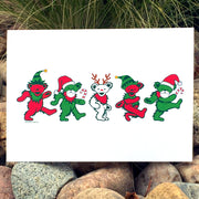 The Jingle Bears greeting card sitting on a bed of river rocks, in front of tall grass