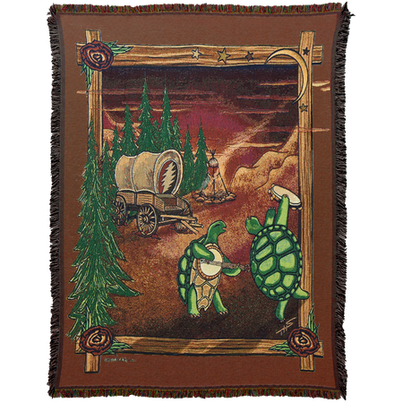 Woven cotton blanket with two terrapin turtles dancing, playing the banjo and the tambourine, with a covered wagon containing a Grateful Dead lightening bolt and a campfire in the background and trees and rocks around the sides, all contained in a wooden frame. Roses are in three corners of the frame, and a crescent moon and stars are in the top right corner, and the border around it is brown.
