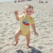 A baby boy toddling on the beach, wearing a yellow Terrapin and Bear infant one piece.