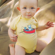 A baby boy sitting on his knees on a yellow blanket, wearing a yellow Terrapin and Bear infant one piece.