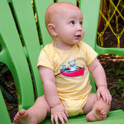A baby boy sitting on a green Adirondack chair, wearing a yellow Terrapin and Bear Dinghy one piece.
