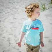 A little boy standing on the beach, looking off to the side, wearing a light blue Terrapin and Bear Dinghy toddler tee.