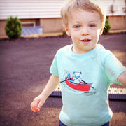 A little boy running around, wearing a light blue Terrapin and Bear Dinghy toddler tee.