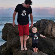 Father and his toddler son standing on large rocks at the beach, wearing matching Dreamcatcher Steal Your Face tshirts.