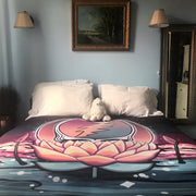 The Lotus Stealie fleece blanket on a bed with white pilllows and a stuffed bear, in front of a blue wall with a picture and two lights above the bed and a full-length mirror next to it.