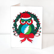A vertical white greeting card that has a green and blue owl with a red face and a Grateful Dead lightning bolt on it's stomach is wearing a red Santa Cap, nestled in a wreath of green roses with red leaves, with a red bow at the bottom