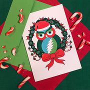 The Holiday Owl greeting card laying with a lime green envelope on top of red and dark green cloth, with broken candy canes sprinkled around it