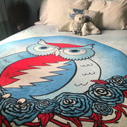 An angled view of the Grateful owl blanket on a bed with white pillows and a stuffed bear at the top