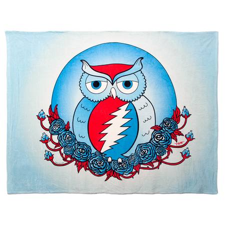 A fleece blanket with a red, white and blue owl with a Grateful Dead lightning bolt on its stomach, nesting on roses with a white and light blue background