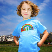 A young girl wearing the blue Rainbow Bears toddler tshirt, showing sass with her hands on her hips, and a blue sky in the background.