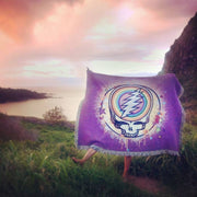 The violet Rainbow Splatter cotton woven blanket being held up in a grassy field, with the ocean in the background