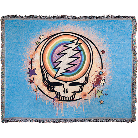 A blue woven cotton blanket with a Grateful Dead Steal Your Face Skull, with a full circle rainbow in the center of the skull, spray paint splatters filling in the circle around it, and dripping around the edges, and stars scattered around the edges of the circle.